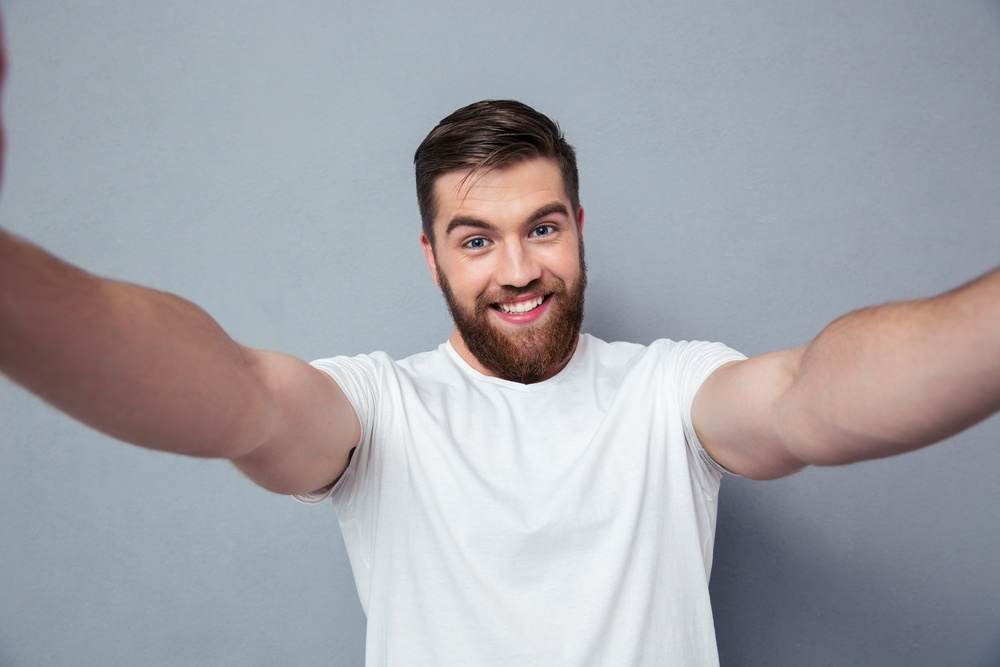 Portrait of a smiling man making selfie photo over gray background.jpeg